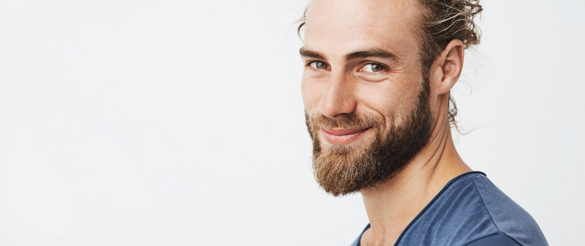 Close up portrait of handsome manly guy with beard posing in three quarters, looking in camera and happily smiling. Lifestyle concept